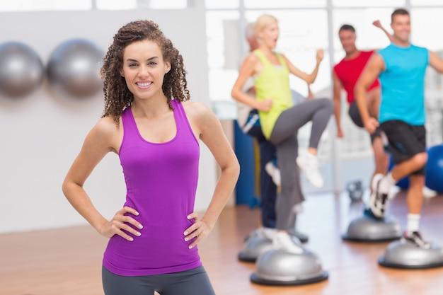 Retrato de feliz mujer de pie las manos en las caderas con personas haciendo ejercicio en el fondo en el gimnasio