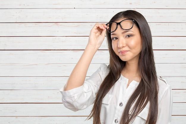 Retrato feliz de la mujer de los vidrios gafas que mira la cámara