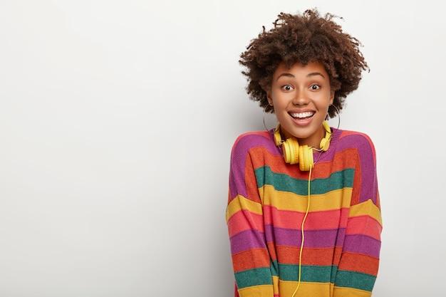 Retrato de feliz niña afro milenaria disfruta de su tiempo libre, escucha música a través de auriculares, te mira feliz