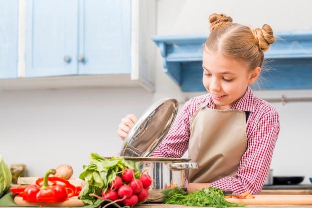 Retrato feliz de una niña mirando acero inoxidable cocina olla en la mesa en la cocina