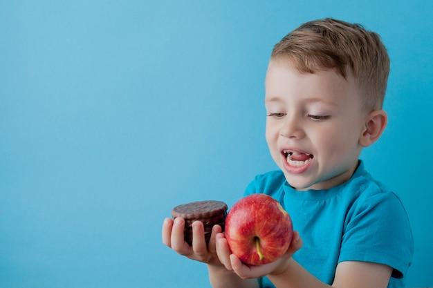 Retrato feliz, niño sonriente elegir comida chatarra. comida sana versus comida no saludable. comida sana vs insalubre, adolescente eligiendo entre galleta o manzana