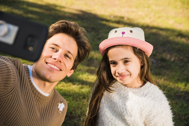 Retrato de un feliz padre e hija tomando selfie