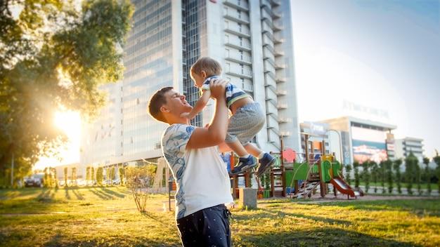 Retrato de feliz padre joven sonriente sosteniendo y vomitando su risa 3 años hijo pequeño en el parque en la susnet