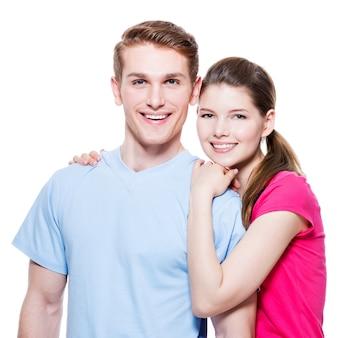 Retrato de la feliz pareja abrazada en casual - aislado en la pared blanca.