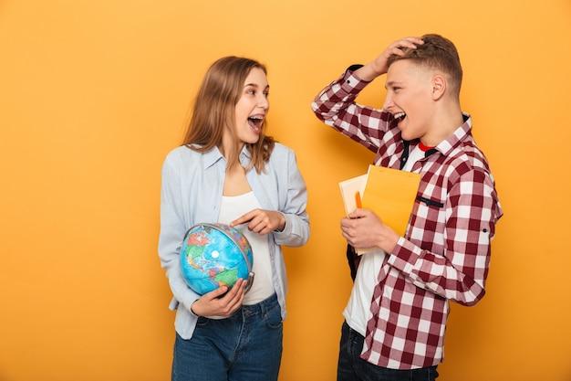 Retrato de una feliz pareja de adolescentes hablando de la escuela