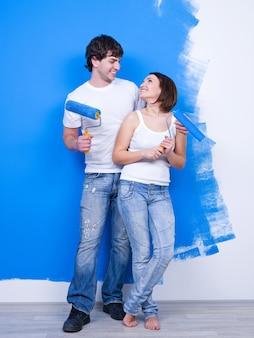 Retrato de feliz pareja alegre amorosa cerca de la pared pintada