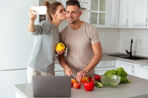 Retrato de una feliz pareja amorosa cocinar ensalada juntos