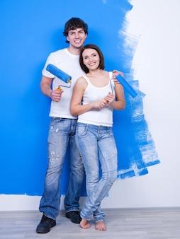 Retrato de feliz pareja amorosa joven con pinceles cerca de la pared pintada