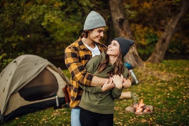 Retrato de la feliz pareja amorosa de turistas en ropa casual en el bosque cerca de la carpa