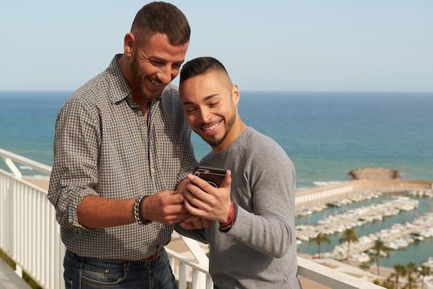 Retrato de una feliz pareja gay al aire libre revisando su teléfono móvil