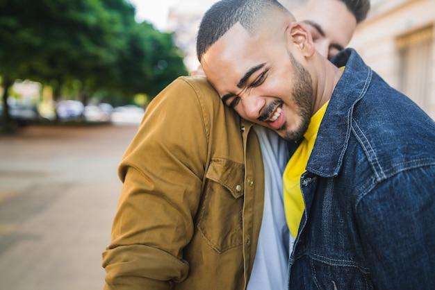 Retrato de feliz pareja gay pasar tiempo juntos y abrazarse en la calle. concepto de amor y lgbt.