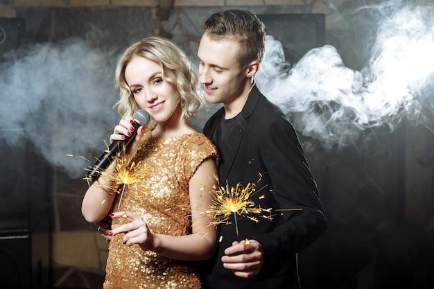 Retrato de la feliz pareja joven con bengalas cantando con micrófono.