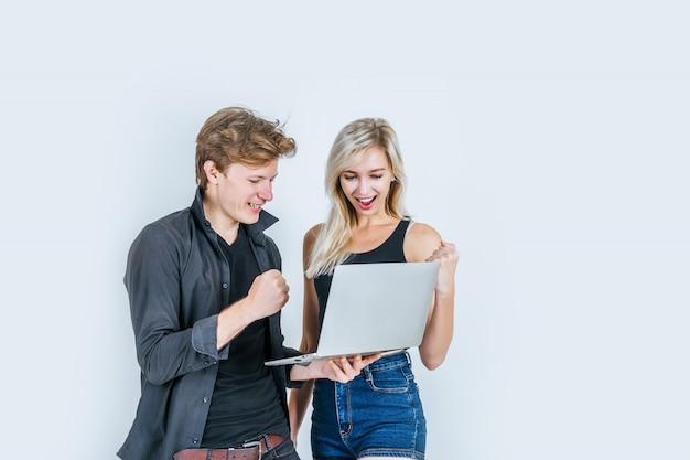 Retrato de la feliz pareja joven usando la computadora portátil