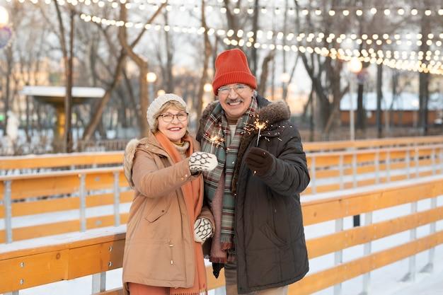 Retrato de feliz pareja madura con luces de bengala sonriendo a la cámara mientras camina en el parque en invierno