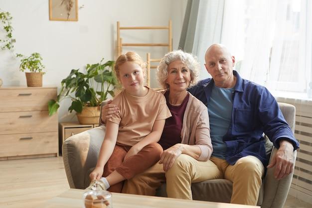 Retrato, de, feliz, pareja mayor, posar, con, lindo, nieta, mientras, sentar sofá, juntos, en, acogedor, hogar, interior