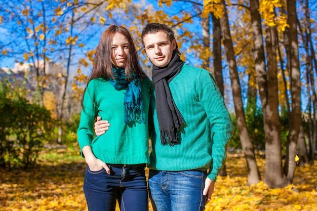 Retrato de la feliz pareja en el parque otoño en un soleado día de otoño