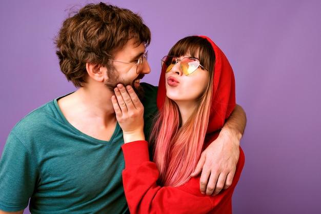 Retrato de feliz pareja romántica hipster divirtiéndose juntos, haciendo besos y abrazos, ropa deportiva brillante casual y gafas de moda, mejores amigos juntos.
