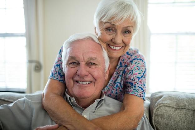 Retrato de la feliz pareja senior abrazándose en la sala de estar en casa
