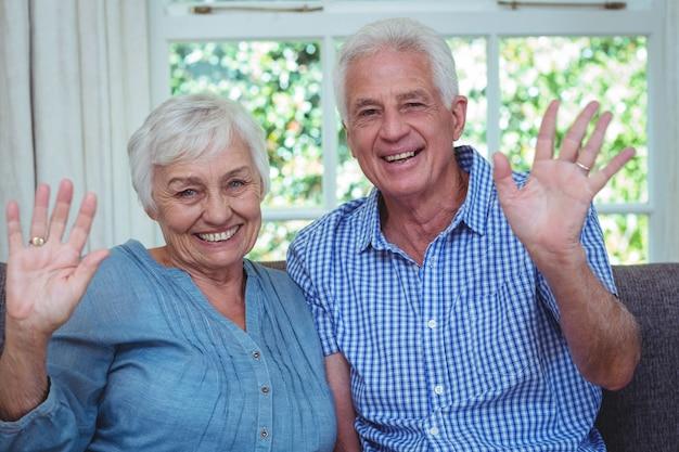 Retrato de la feliz pareja senior agitando la mano