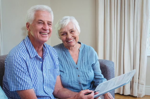 Retrato de la feliz pareja senior con facturas