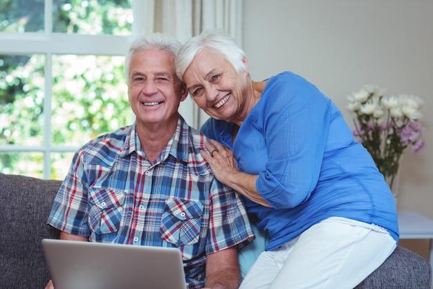 Retrato de la feliz pareja senior usando laptop
