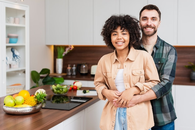 Retrato de la feliz pareja sentada en la cocina
