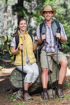 Retrato de la feliz pareja sentada en la roca durante el senderismo