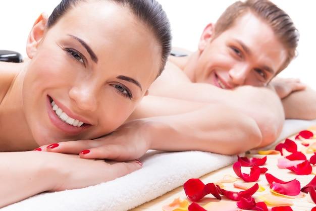 Retrato de feliz pareja sonriente relajante en el salón de spa con piedras calientes en el cuerpo.