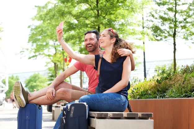 Retrato de la feliz pareja de viajeros que toman selfie fuera en el parque