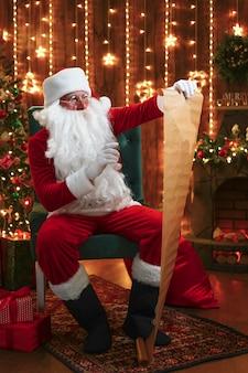 Retrato de feliz santa claus sentado en su habitación en casa cerca del árbol de navidad y leyendo la carta de navidad o la lista de deseos