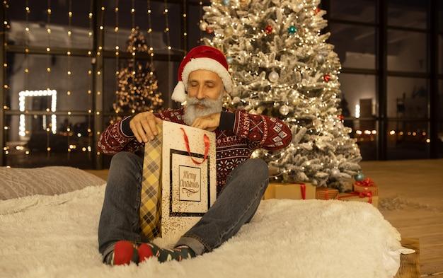 Retrato de feliz santa claus en su habitación en casa cerca del árbol de navidad.