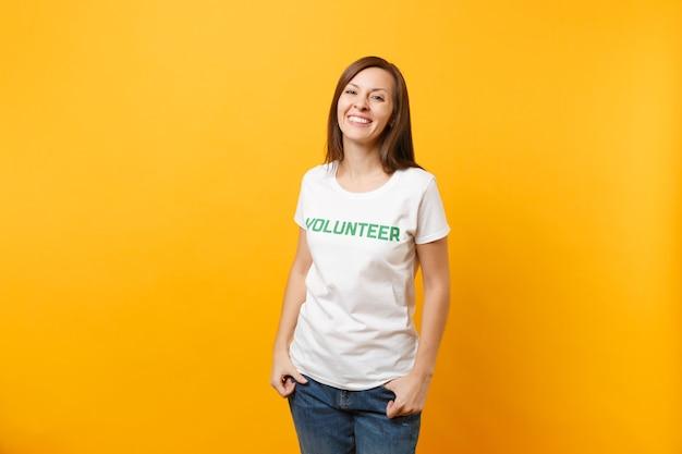 Retrato de feliz sonriente mujer satisfecha en camiseta blanca con inscripción escrita voluntario de título verde aislado sobre fondo amarillo. ayuda de asistencia gratuita voluntaria, concepto de trabajo de gracia de caridad.