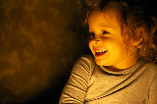 Retrato de una feliz y sonriente niña pelirroja en los cálidos rayos amarillos de una lámpara en el cuarto oscuro.