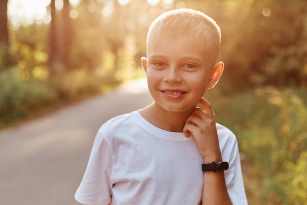 Retrato de feliz sonriente niño rubio con camiseta blanca casual, mirando directamente a la cámara con una gran sonrisa, manteniendo la mano en el cuello, pasando tiempo en el parque de verano al atardecer.