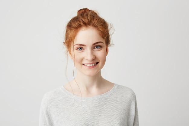 Retrato de feliz tierna niña de jengibre con ojos azules y pecas sonriendo.