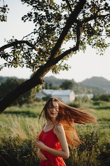 Retrato femenino encantadora mujer en vestido rojo se encuentra bajo el ol