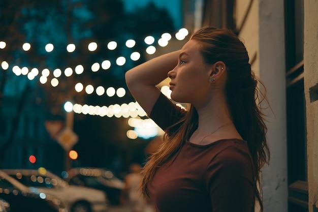 Retrato femenino romántico con luces de la ciudad