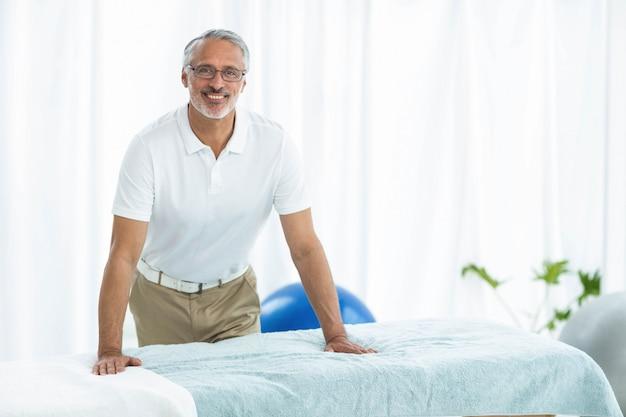 Retrato de fisioterapeuta sonriendo y de pie junto a la mesa de masaje en casa