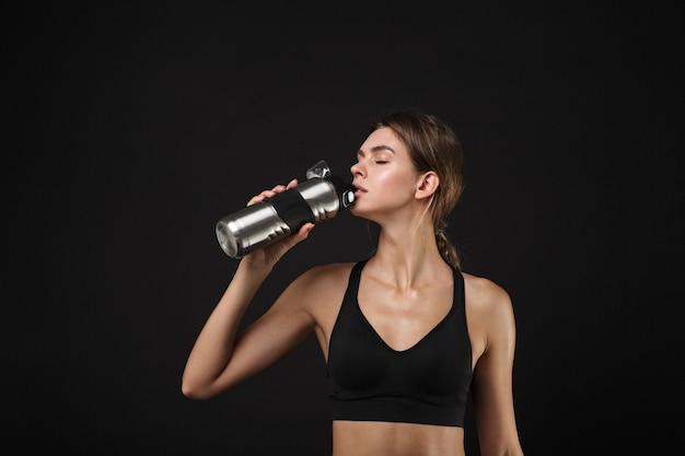 Retrato de fitness mujer caucásica en ropa deportiva bebiendo agua de botella durante el entrenamiento en el gimnasio aislado sobre fondo negro