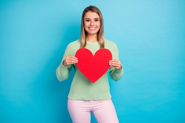 Retrato fotográfico de una bella dama en suéter verde sosteniendo un gran corazón rojo aislado sobre fondo azul.