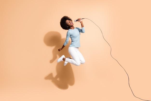 Retrato fotográfico de una chica afroamericana loca sosteniendo el micrófono en una mano cantando en el aire aislado sobre fondo de color beige pastel