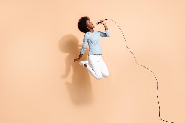 Retrato fotográfico de mujer afroamericana salvaje sosteniendo el micrófono en una mano cantando en el aire aislado sobre fondo de color beige pastel