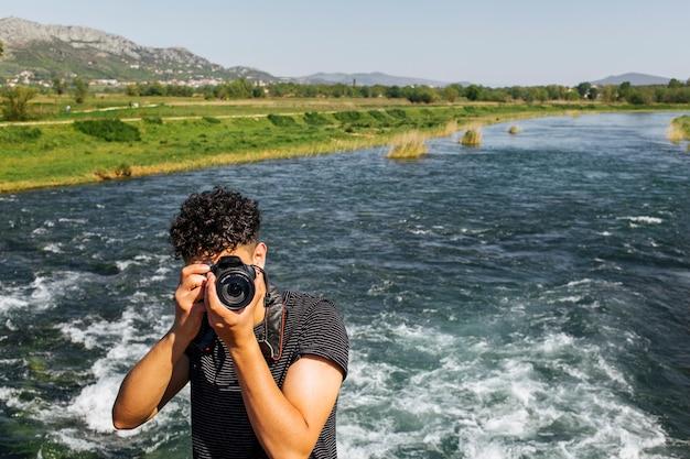 Retrato del fotógrafo joven que toma la foto delante de cámara