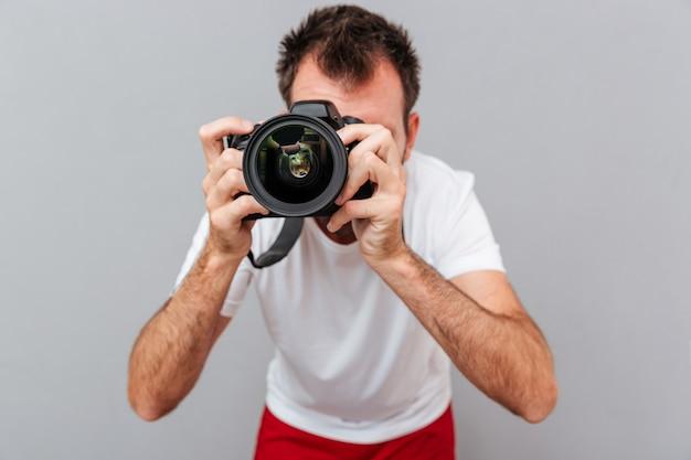 Retrato de un fotógrafo masculino con cámara tomando fotos aislado sobre un fondo gris