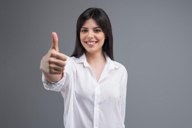 Retrato de un freelancer sonriente feliz de la mujer de negocios que muestra los pulgares para arriba aislados sobre fondo gris