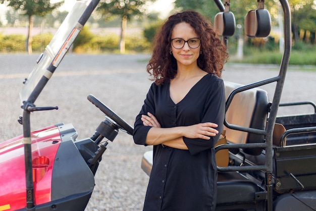 El retrato frontal de una mujer alegre con las manos cruzadas posa cerca del exterior del vehículo. vista horizontal.