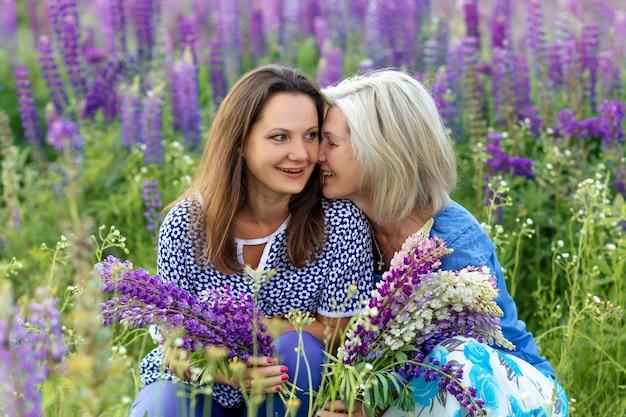 Retrato de generación familiar: feliz abuela e hija en un floreciente campo de lupino. concepto del día de la madre