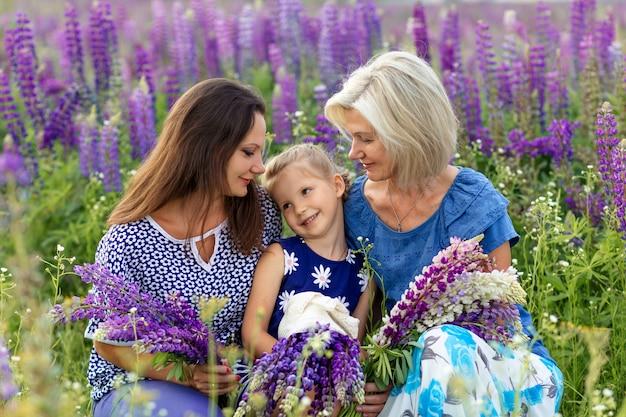 Retrato de generación familiar: feliz abuela, hija y nieta en un floreciente campo de lupino. concepto del día de la madre
