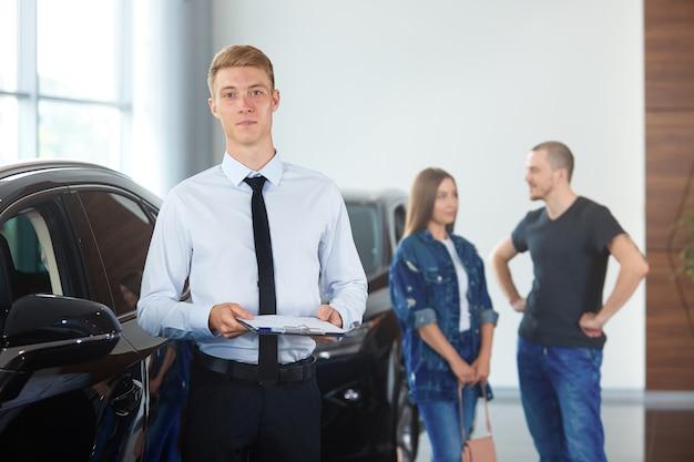 Retrato de un gerente en un concesionario de automóviles con el trasfondo de automóviles y compradores