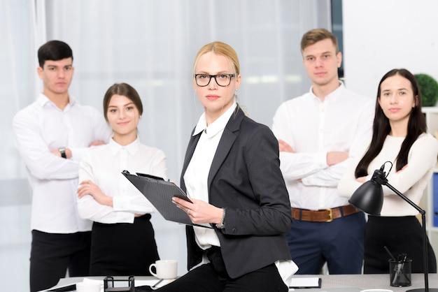 Retrato de una gerente femenina con portapapeles en la mano con su colega en el lugar de trabajo